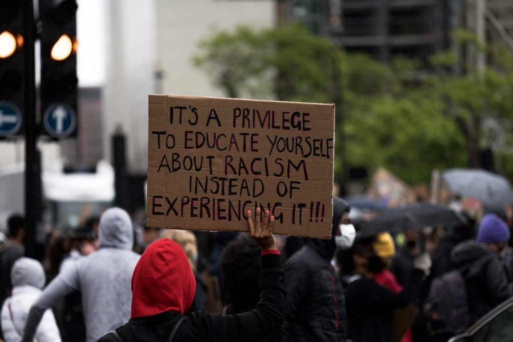 Sign saying 'It's a privilege to educate yourself about racism instead of experiencing it!!'